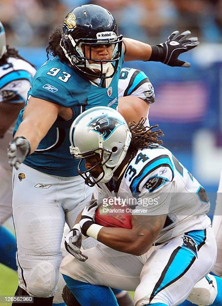Carolina Panthers running back DeAngelo Williams tries to duck under the arms of Jacksonville Jaguars defensive tackle Tyson Alualu on a run during...