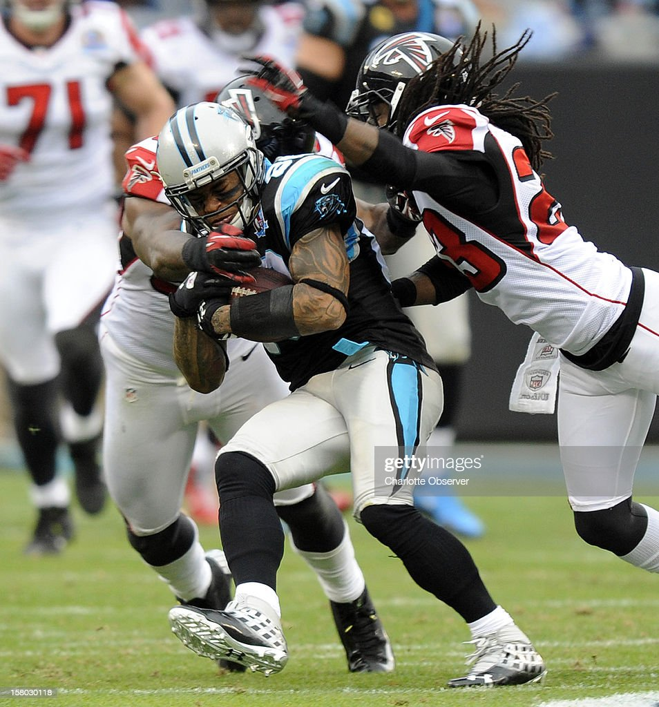 Carolina Panthers' Steve Smith (89) secures the ball as Atlanta Falcons' Akeem Dent (52) and Dunta Robinson (23) apply pressure during the first half at Bank of America Stadium on Sunday, December 9, 2012, in Charlotte, North Carolina.