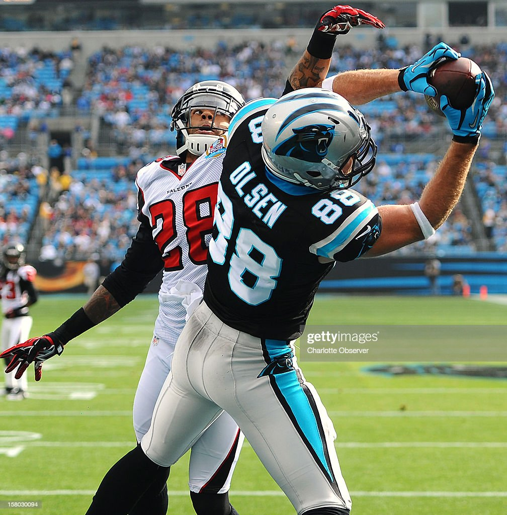 Carolina Panthers tight end Greg Olsen (88) catches a touchdown pass against Atlanta Falcons safety Thomas DeCoud (28) during first-quarter action at Bank of America Stadium on Sunday, December 9, 2012, in Charlotte, North Carolina.