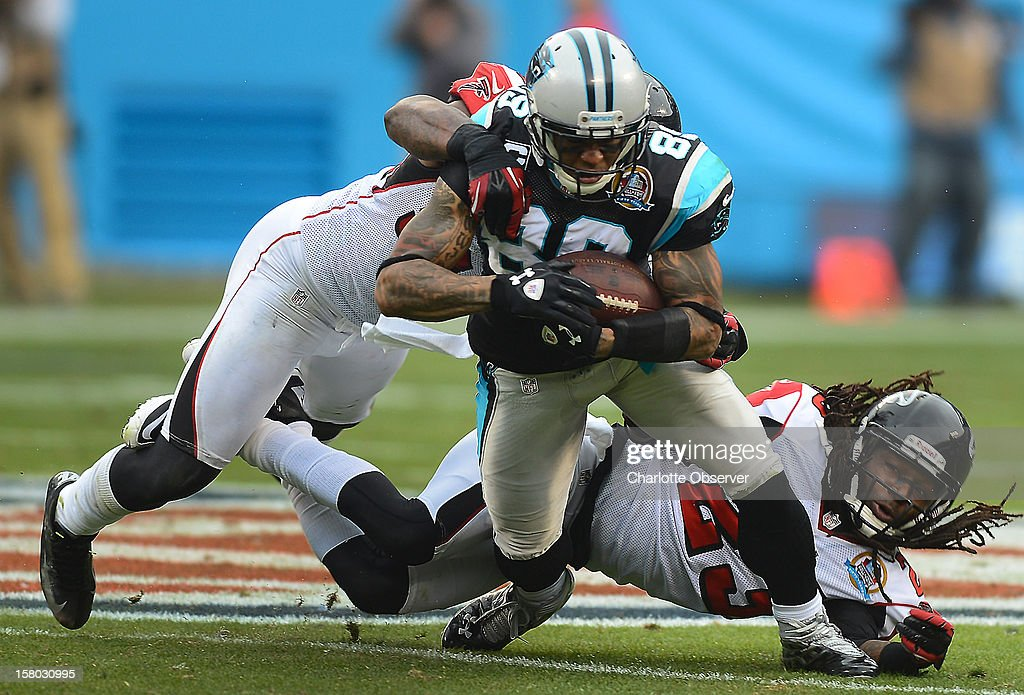 Carolina Panthers wide receiver Steve Smith (89) fights for yardage following a pass reception against Atlanta Falcons linebacker Akeem Dent (52) and cornerback Dunta Robinson (23) during second-quarter action at Bank of America Stadium on Sunday, December 9, 2012, in Charlotte, North Carolina.
