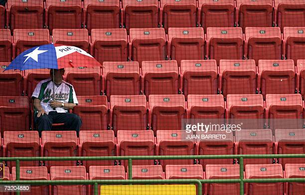 A baseball fan waits at the stand for the beginning of the game between Venezuela and Mexico during the Caribbean Series at the Roberto Clemente...