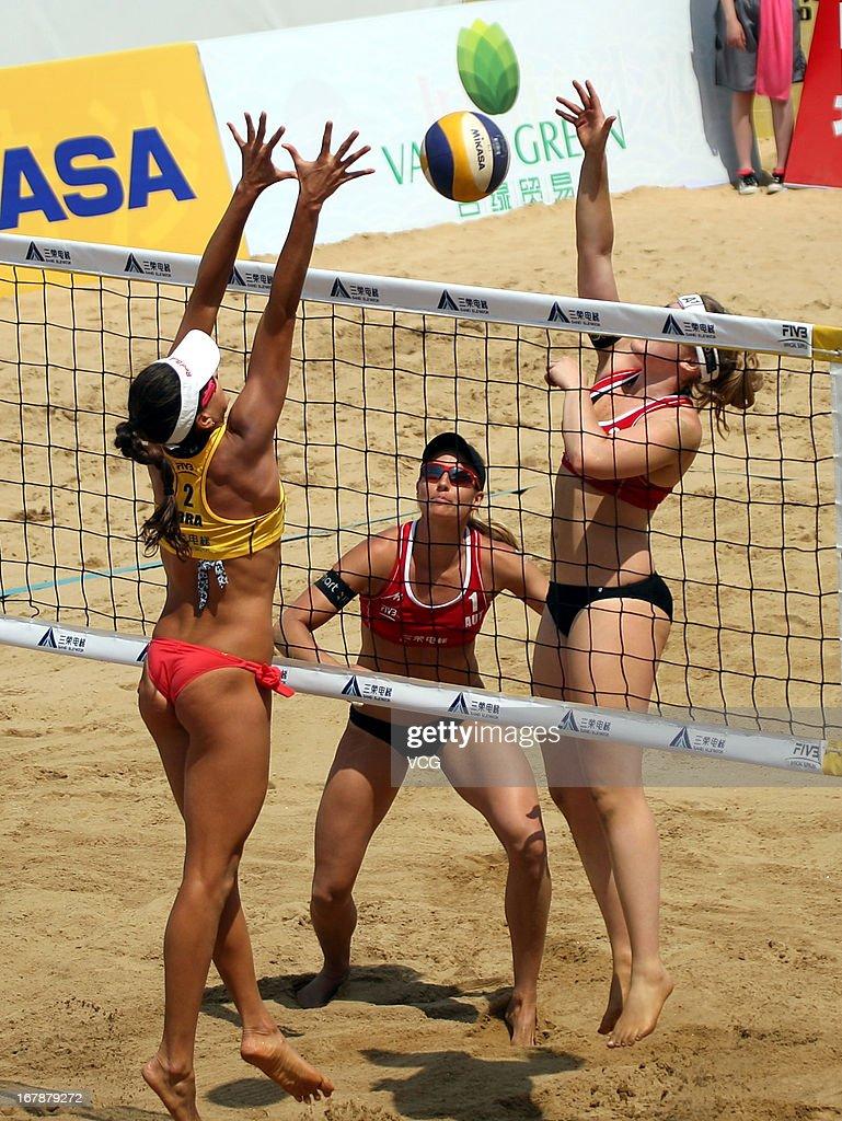 Carolina Solberg Salgado (L) of Brazil defends against Barbara Hansel (C) and Katharina Schutzenhofer (R) of Austria during the women's qualification of FIVB Beach Volleyball Shanghai Grand Slam at Jinshan City Beach on May 1, 2013 in Shanghai, China.