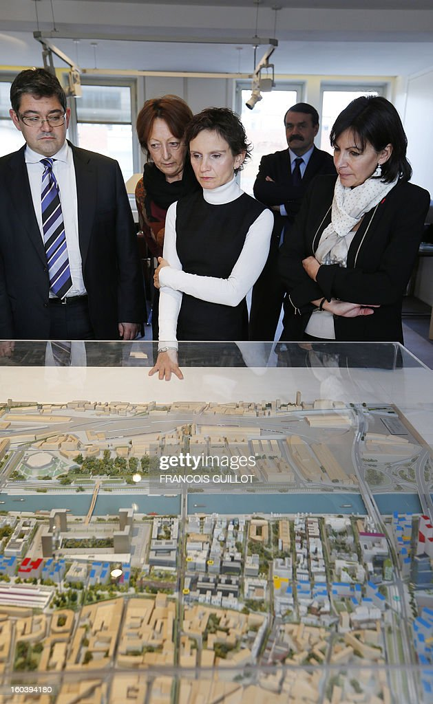 Carolina Toha (C), mayor of Santiago in Chile, looks at a model of building projects beside Paris' deputy Mayor and socialist party candidate for the 2014 municipal elections, Anne Hidalgo (R) during their joint visit to the 'Paris Rive Gauche' construction project site on January 30, 2013 in Paris. AFP PHOTO FRANCOIS GUILLOT