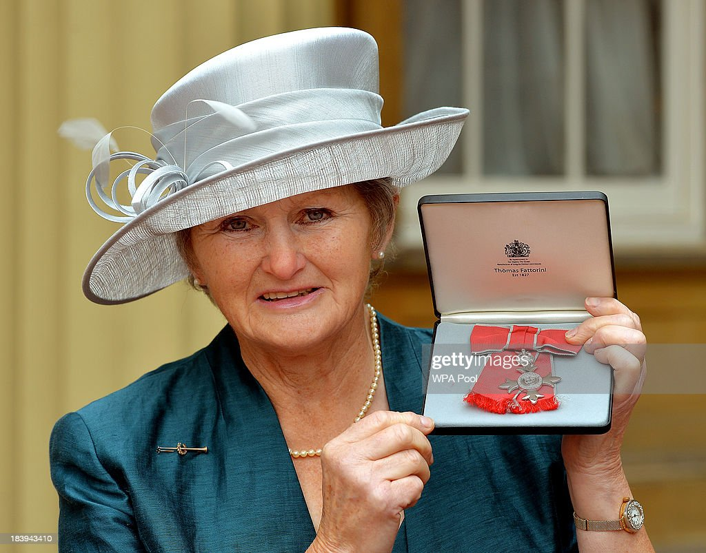 Caroline Dale-Leech holding her MBE after it was presented to her by Queen Elizabeth II at an Investiture Ceremony at Buckingham Palace on October 10, 2013 in London, England.