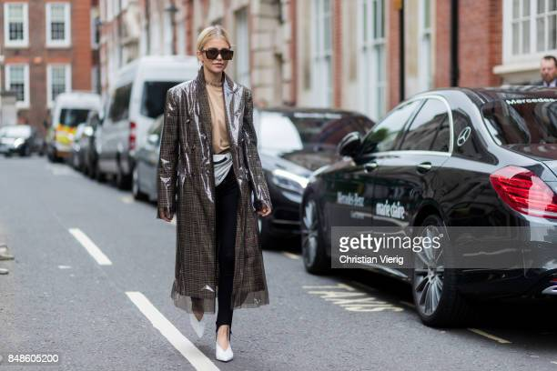 Caroline Daur wearing a checked Calvin Klein coat belt bag outside Preen during London Fashion Week September 2017 on September 17 2017 in London...