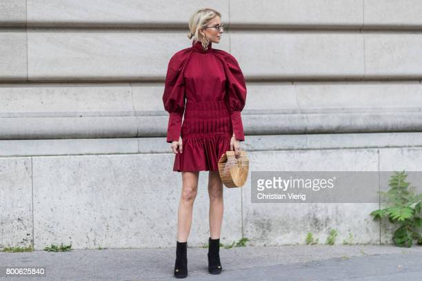 Caroline Daur wearing a red dress black boots basket bag outside Dior Homme during Paris Fashion Week Menswear Spring/Summer 2018 Day Four on June 24...