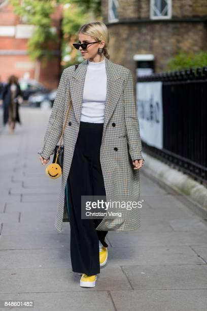 Caroline Daur wearing flared pants checked coat outside Anya Hindmarch during London Fashion Week September 2017 on September 17 2017 in London...