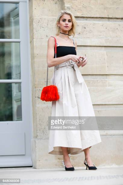 Caroline Daur wears a black off shoulder top a red fur bag and a white skirt and black heels outside the Christian Dior show as part of the Paris...
