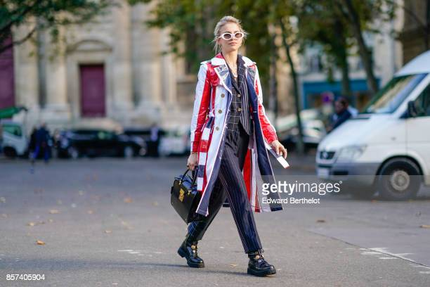 Caroline Daur wears a blue red white striped leather jacket outside Thom Browne during Paris Fashion Week Womenswear Spring/Summer 2018 on October 3...