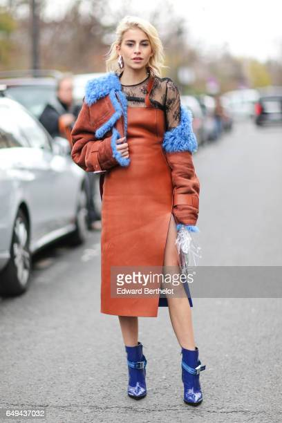Caroline Daur wears a brown aviator jacket with blue fur a brown leather dress blue heels outside the Moncler Gamme Rouge show during Paris Fashion...