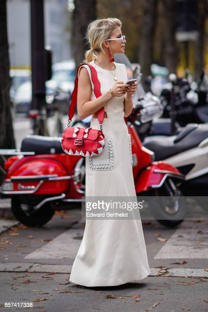 Caroline Daur wears a white dress a red bag outside Moncler during Paris Fashion Week Womenswear Spring/Summer 2018 on October 3 2017 in Paris France