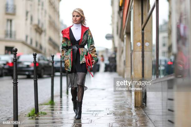 Caroline Daur wears a white turtleneck a multicolor winter jacket with a hood and red inner lining a black lace dress black fishnet tights and black...