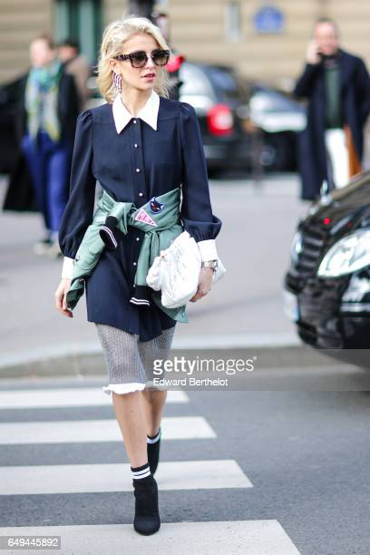 Caroline Daur wears sunglasses a long blue shirt with white collar a green Miu Miu bomber jacket a skirt and black shoes outside the Miu Miu show...