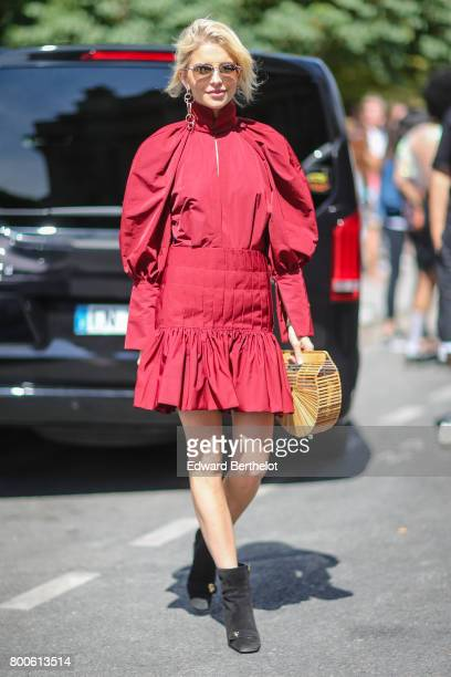 Caroline Daur wears sunglasses a red dress a semi circular bag and black shoes outside the Dior show during Paris Fashion Week Menswear Spring/Summer...