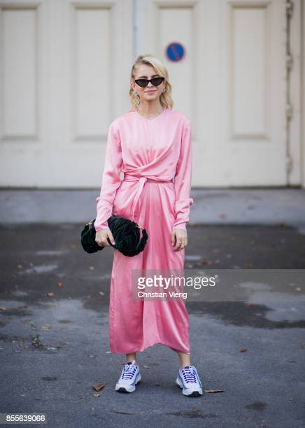 Caroline Daur with braid hair wearing pink silk Celine overall is seen outside Issey Miyake during Paris Fashion Week Spring/Summer 2018 on September...