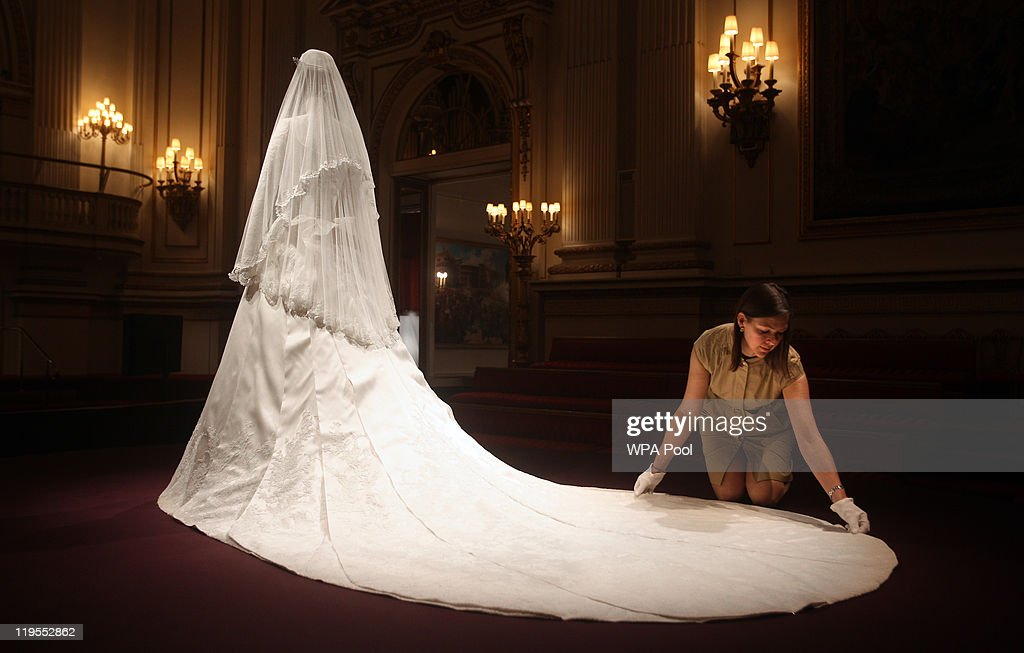 Caroline de Guitaut, curator of the exhibition display adjusts the Duchess of Cambridge's wedding dress, designed by Sarah Burton for Alexander McQueen, before it goes on exhibit at Buckingham Palace during the annual summer opening on July 20, 2011 in London, England. The Duchess of Cambridge's dress featured lace appliqué floral detail and was made of ivory and white satin gazar with a 9ft train. It was worn her wedding day on April 29 to Prince William, Duke of Cambridge.