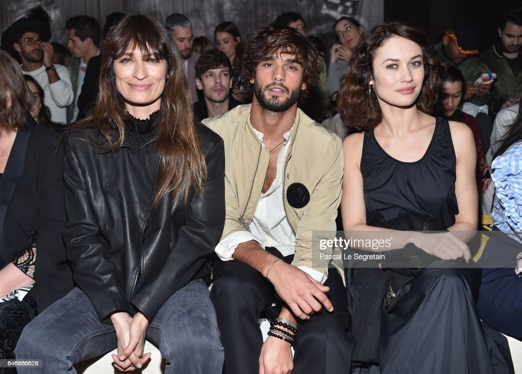 Caroline de Maigret, Marlon Teixeira and Olga Kurylenko attend the H&M Studio show as part of the Paris Fashion Week on March 1, 2017 in Paris, France.