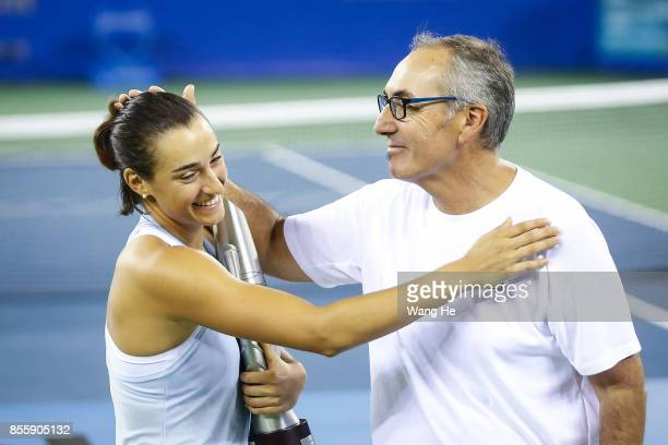 Caroline Garcia celebrates with her father and coach Louis Paul Garcia at the award ceremony after winning the ladies singles final between Ashleigh...