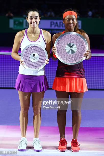 Caroline Garcia of France and Naomi Osaka of Japan hold their trophies after the WTA Rising Stars Final at Singapore Sports Hub on October 25 2015 in...