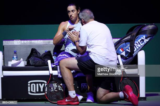 Caroline Garcia of France confers with her father and coach Louis Paul Garcia between games against Simona Halep of Romania during day 2 of the BNP...