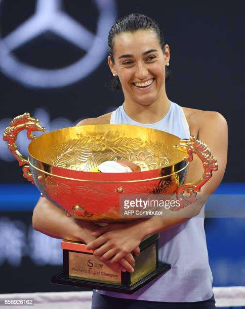 Caroline Garcia of France holds the trophy after winning the women's singles final against Simona Halep of Romania at the China Open tennis...
