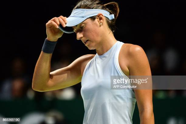 Caroline Garcia of France reacts on a point against Simona Halep of Romania during the WTA Finals tennis tournament in Singapore on October 23 2017 /...