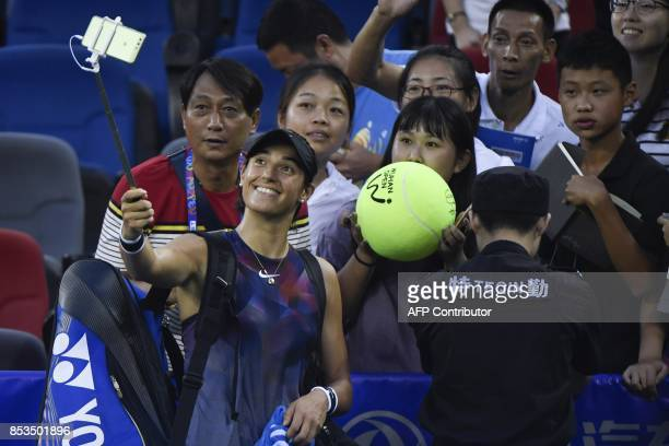 Caroline Garcia of France uses a mobile phone to take a group photo with fans after winning against Angelique Kerber of Germany during their first...