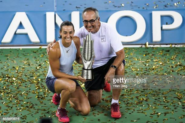 Caroline Garcia poses with her father and coach Louis Paul Garcia at the award ceremony after winning the ladies singles final between Ashleigh Barty...