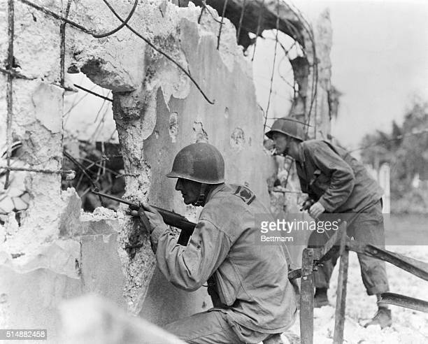 Two members of the 81st Division U S Army explore a Japanese pillbox smashed by prelanding fire from Navy vessels Scene is on Ulithi Atell in the...