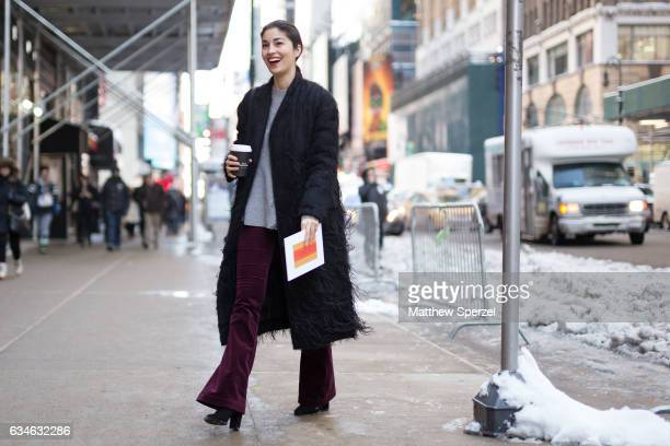 Caroline Issa is seen attending Calvin Klein during New York Fashion Week wearing a long black coat with fringe and merlot pants on February 10 2017...
