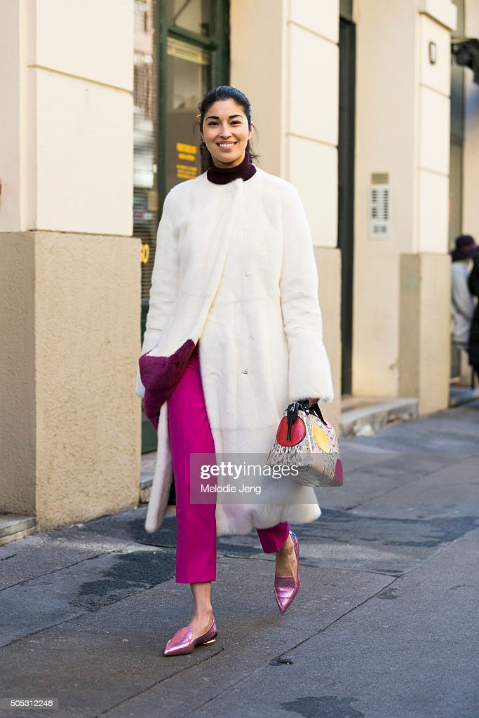 Caroline Issa wears a white fur Gabriele Colangelo coat with fuscia trousers pink metallic flats and a Fendi purse and during the Milan Men's Fashion...