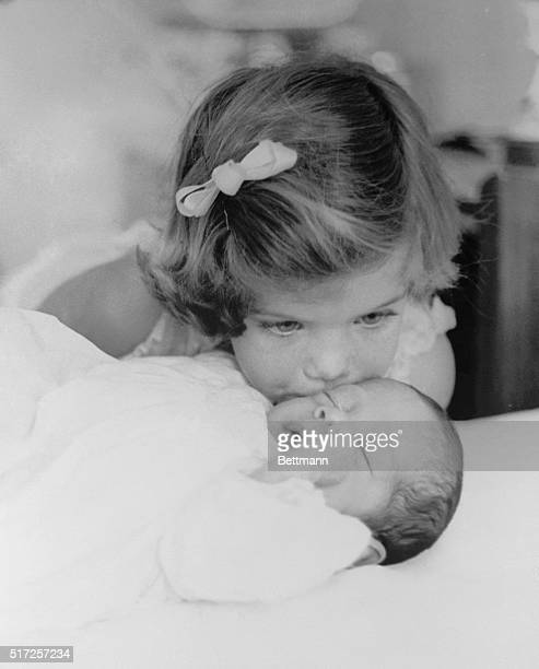 Caroline Kennedy kisses her new brother John F Kennedy Jr in this picture made during the Kennedys' preinaugural stay in Palm Beach Florida It is one...