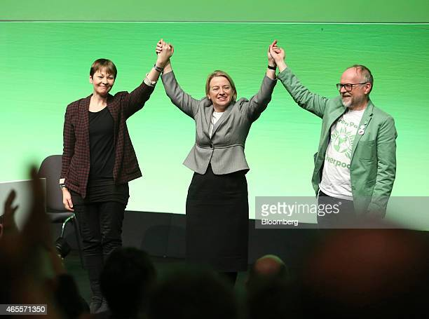 Caroline Lucas member of parliament for the Green Party left stands on stage with Natalie Bennett leader of the Green Party center and Martin Dobson...