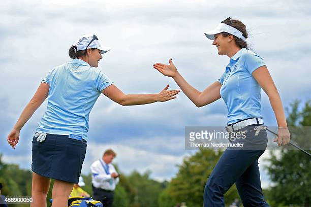 Caroline Masson and Sandra Gal of the European Team shake hands during the afternoon fourball matches on day one of the Solheim Cup 2015 at St...