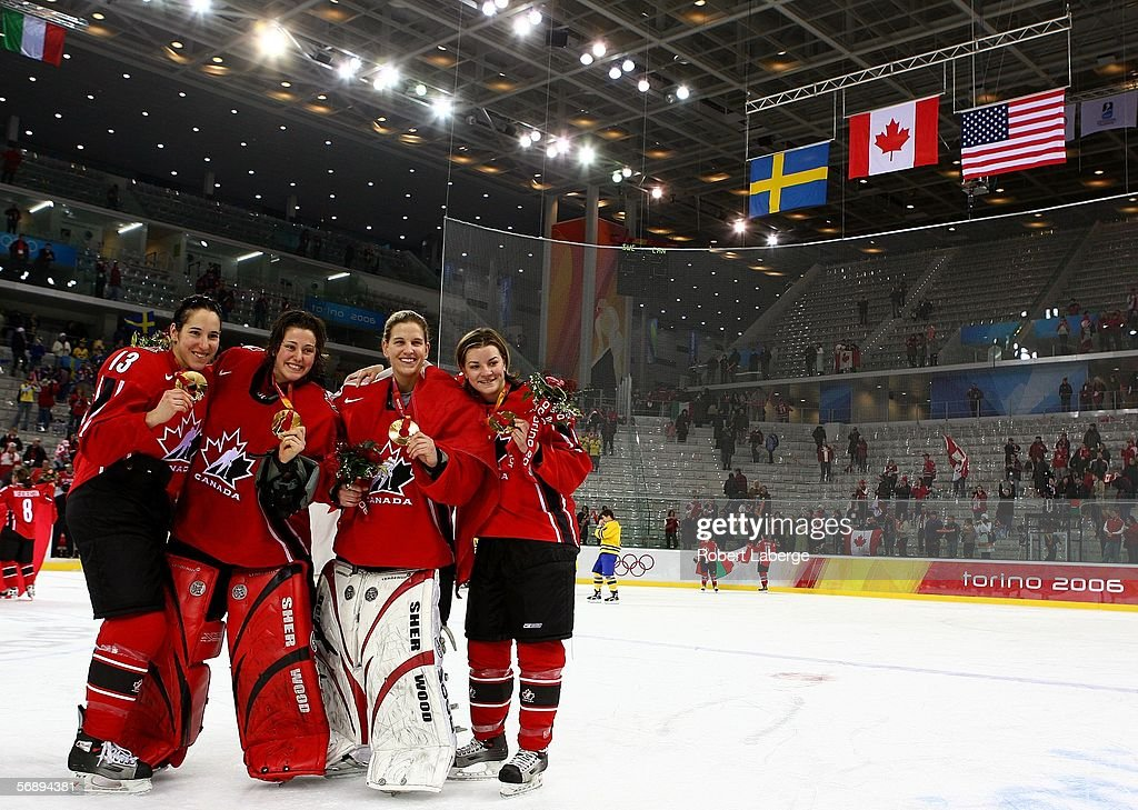 Caroline Ouellette #13, Charline Labonte #32, Kim St-Pierre #33 and Sarah Vaillancourt #26 of Canada pose for a picture after receiving the gold medal following their 4-1 victory over Sweden in the final of the women's ice hockey on Day 10 of the Turin 2006 Winter Olympic Games on February 20, 2006 at the Palasport Olimpico in Turin, Italy.