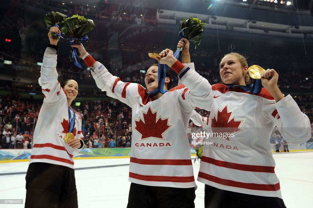 <a gi-track='captionPersonalityLinkClicked' href=/galleries/search?phrase=Caroline+Ouellette&family=editorial&specificpeople=722185 ng-click='$event.stopPropagation()'>Caroline Ouellette</a> #13, Sarah Vaillancourt #26 and <a gi-track='captionPersonalityLinkClicked' href=/galleries/search?phrase=Tessa+Bonhomme&family=editorial&specificpeople=5805856 ng-click='$event.stopPropagation()'>Tessa Bonhomme</a> #25 of Canada celebrate after receiving the gold medals won during the ice hockey women's gold medal game between Canada and USA on day 14 of the Vancouver 2010 Winter Olympics at Canada Hockey Place on February 25, 2010 in Vancouver, Canada.