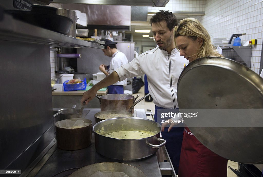 Caroline Rostang looks at stew pots in the kitchen of her father's restaurant the 'Michel Rostang' on November 23, 2012 in Paris.