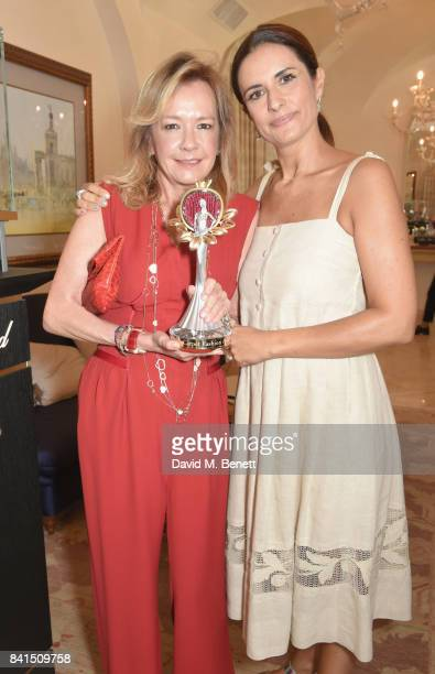 Caroline Scheufele and Livia Firth pose with the Green Carpet Fashion Award as they attend an intimate lunch to announce Chopard as partner for The...