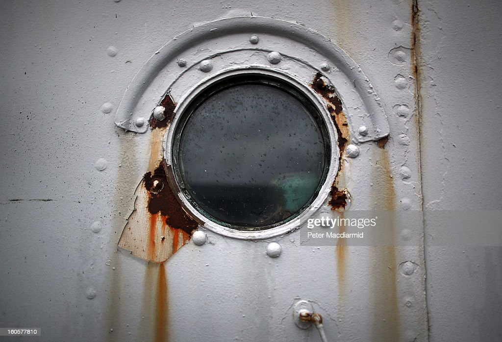 Caroline shows some rust and flaking paintwork on one of her portholes on January 29, 2013 in Belfast, Northern Ireland. A National Heritage Memorial Fund grant of 1.097 m GBP will go towards urgent preventative work to secure the Caroline. An application for more funding is being made in order to proceed with full restoration of the 446 ft ship. Built by Cammell Laird at Birkenhead in 1914 she was part of the 4th Light Cruiser Squadron which saw action in the Battle of Jutland in 1916 and is the last surviving Royal Navy ship from that period still afloat. At the time of her decommissioning in 2011, she was the second oldest ship still in Royal Navy service, HMS Victory Nelson's flagship preserved at Portsmouth, being the oldest. Caroline was converted into a depot and training ship for The Royal Navy Reserve in Alexandra Dock in Belfast in later years.