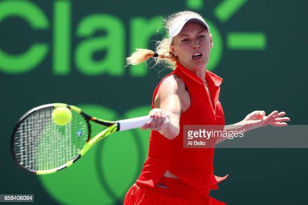 Caroline Wosniacki of Denmark returns a shot against Garbine Muguruza of Spain during Day 8 of the Miami Open at Crandon Park Tennis Center on March...