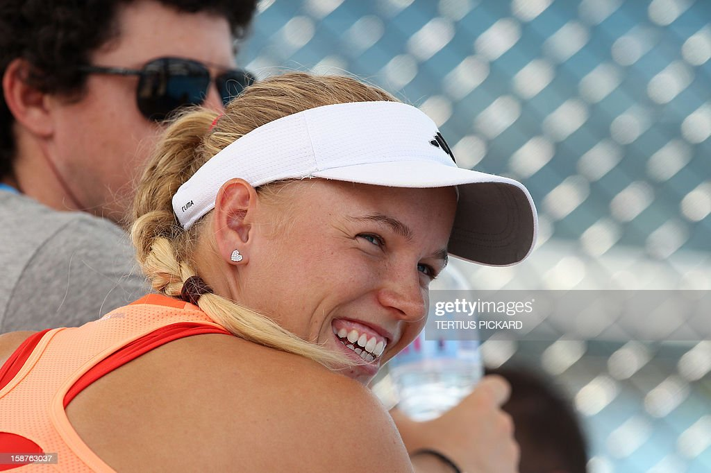 Caroline Wozniacki of Denmark and her boyfriend, golfer Rory Mcllroy (L) of Northern Ireland, are pictured during her training session in Brisbane on December 28, 2012, for the upcoming Brisbane International tennis tournament. The top international men's and women's players are using the Brisbane International as a build-up to the Australian Open, which runs from January 14 to 27. AFP PHOTO / Tertius PICKARD USE
