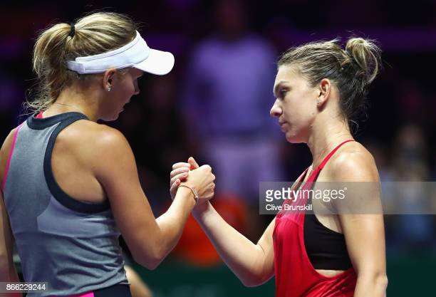 Caroline Wozniacki of Denmark celebrates victory as she shakes the hand of Simona Halep of Romania after their singles match during day 4 of the BNP...