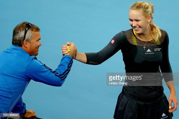 Caroline Wozniacki of Denmark celebrates with her coach and father Piotr Wozniacki after her win over Vera Zvonareva of Russia in the final on day...