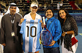 Caroline Wozniacki of Denmark exchanges gifts with football legend Diego Maradona as they pose for a picture with Salah Tahlak Tournament Director...