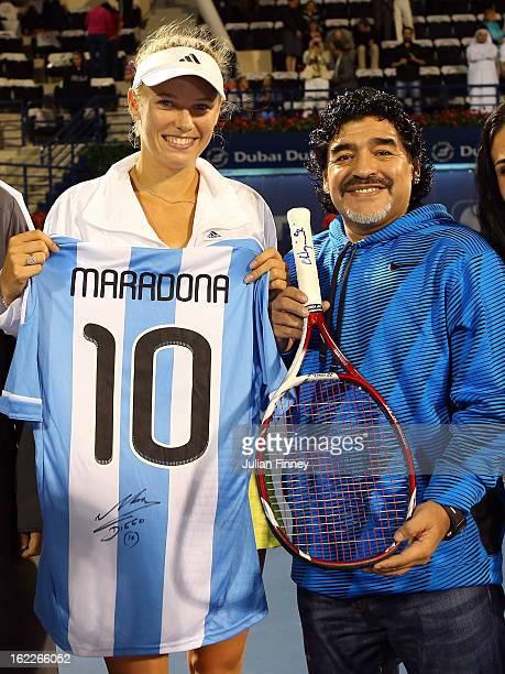 Caroline Wozniacki of Denmark exchanges gifts with football legend Diego Maradona as they pose for a photo during day four of the WTA Dubai Duty Free...