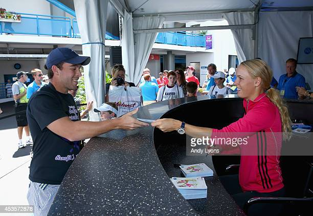Caroline Wozniacki of Denmark hands out autographs on day 5 at Western Southern Open on August 13 2014 at the Linder Family Tennis Center in...