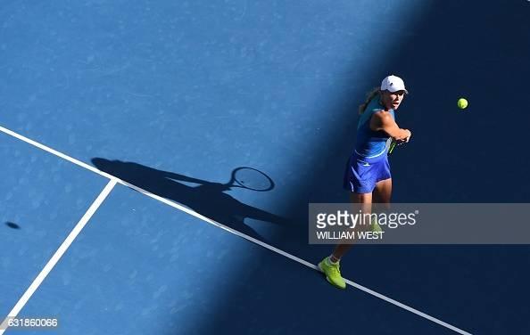 TOPSHOT Caroline Wozniacki of Denmark hits a return against Arina Rodionova of Australia during their women's singles match on day two of the...