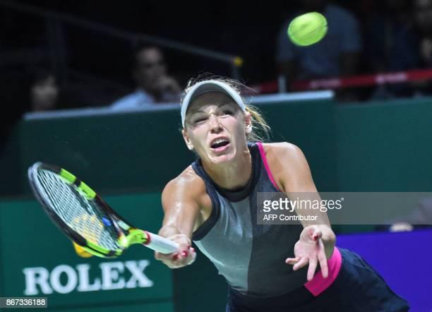 Caroline Wozniacki of Denmark hits a return against Karolina Pliskova of Czech Republic during the WTA Finals tennis tournament in Singapore on...