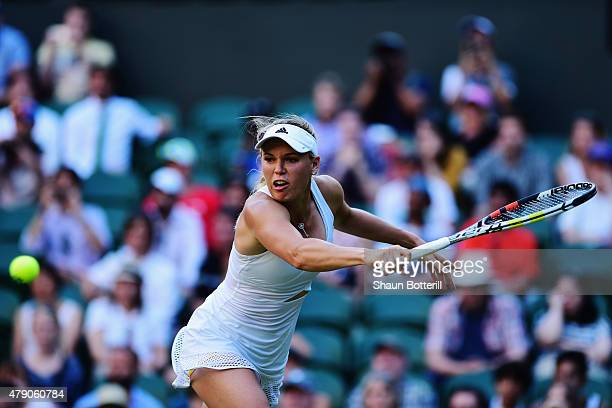 Caroline Wozniacki of Denmark in action in her Ladies Singles first round match against Saisai Zheng of China during day two of the Wimbledon Lawn...