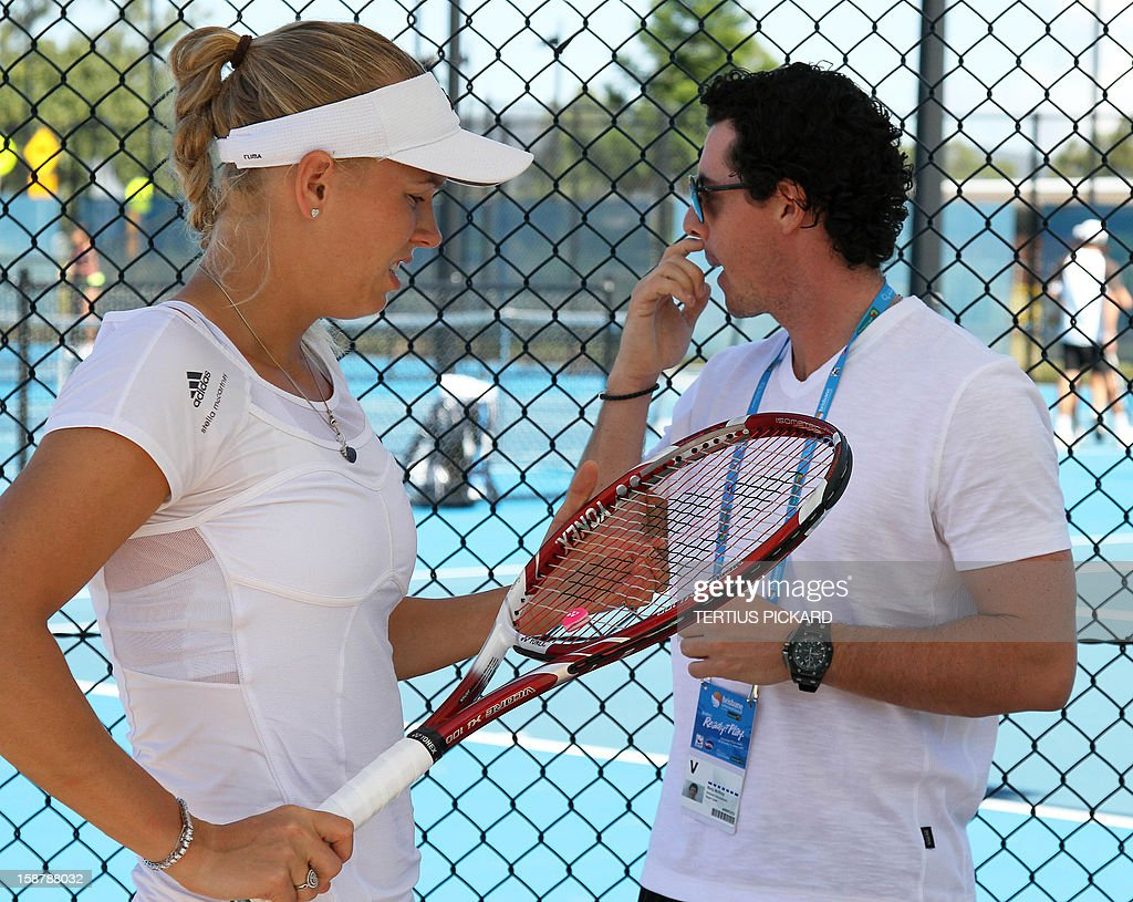 Caroline Wozniacki of Denmark (L) is pictured with her boyfriend, world number one golfer Rory McIlroy of Northern Ireland (R) before her training session in Brisbane on December 29, 2012, ahead of the upcoming Brisbane International tennis tournament. Top international men's and women's players are using the Brisbane International as a build-up to the Australian Open, which runs from January 14 to 27. AFP PHOTO/Tertius PICKARD USE
